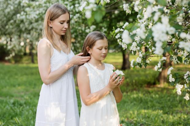 Молодая девушка в белом платье заплетает волосы другой юной девушке в светлом наряде