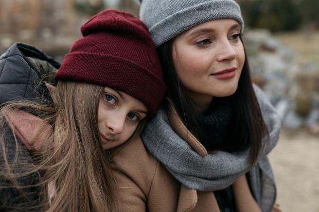 девочка положила голову на плечо женщине