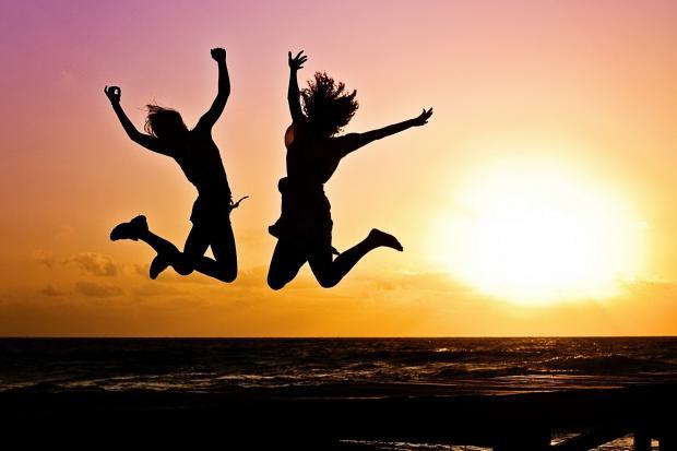 две фигуры в прыжке на фоне заката