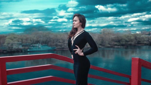 девушка в черном облегабщем платье с идеальной фигурой стоит на фоне красивого природного пейзажа
