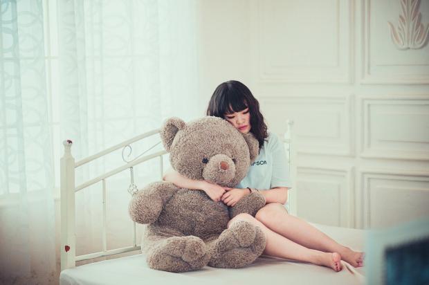 девушка в обнимку с большим плюшевым мишкой сидит на кровати белой