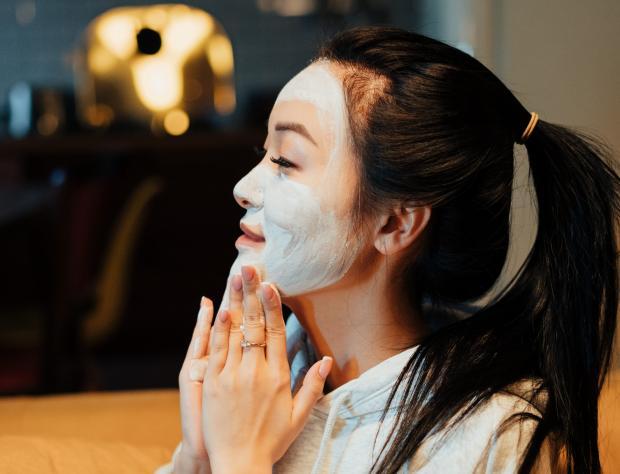 Девушка с темными волосами наносит маску на кожу лица