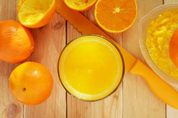 Апельсиновый сок в стакане и порезанные апельсины на столе