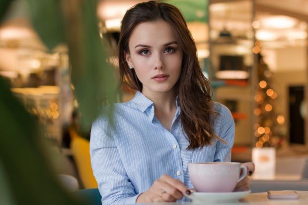 девушка в голубой рубашке с чашкой кофе