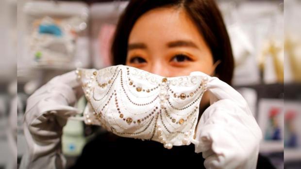 Молодая девушка держит в руках белую маску для лица