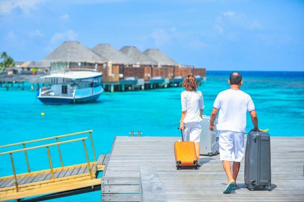 Мужчина и женщина с чемоданами идут по деревянному причалу к голубому морю