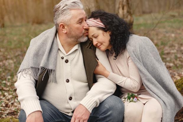 Взрослый мужчина и женщина сидят на природе