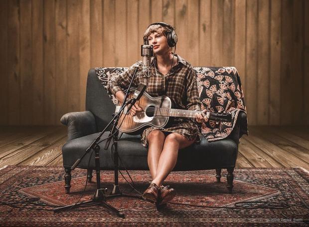 Тейлор Свифт сидит на диване с гитарой