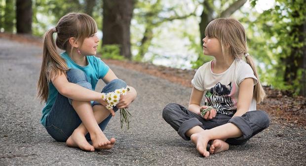 дети сидят на земле в позе лотоса