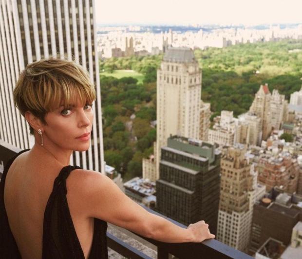 Шарлиз Терон с короткой стрижкой позирует на балконе на фоне красивого вида на город