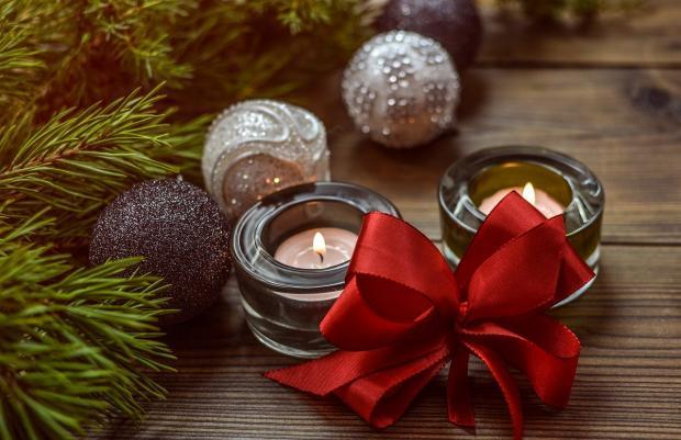 горячие свечи с красным бантом и игрушками шарами у новогодней елки
