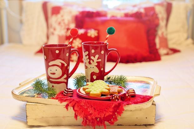 две красных кружки с рождественской тематикой на подносе с печеньем