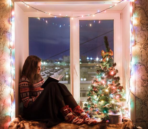 девушка сидит на подоконнике с новогодней елкой и читает книгу