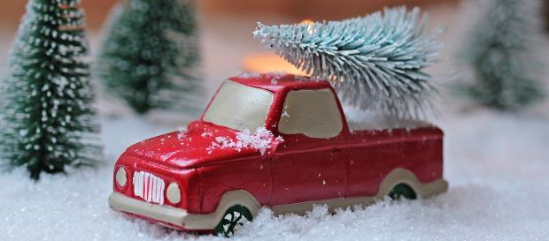 игрушечный красный автомобиль с нагруженной новогодней елкой