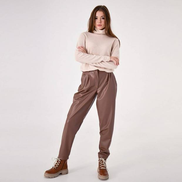 Девушка в кожаных брюках и светлом свитере