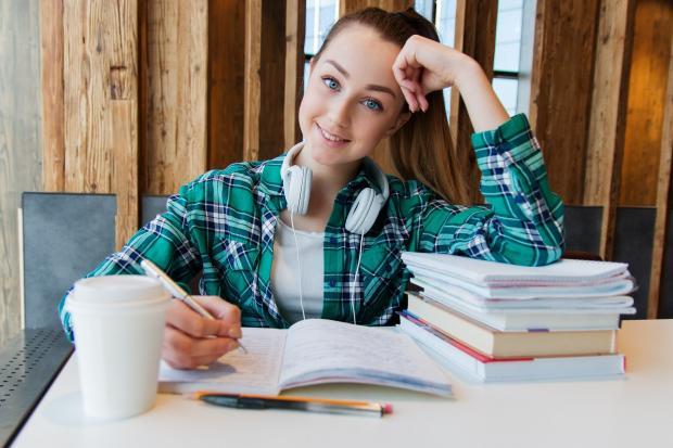 улыбающаяся девушка сидит перед учебниками
