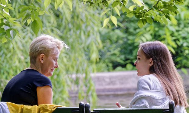 девушка и женщина общаются, сидя на скамейке
