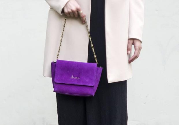 девушка в светлом пальто держит в руках сиреневую сумку