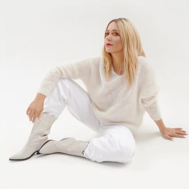 Наталья Могилевская в белом свитере и светлых брюках