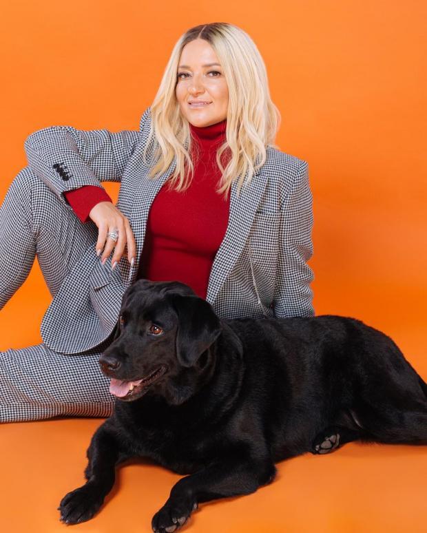 Наталья Могилевская в клетчатом костюме и красной водолазке сидит возле черной собаки