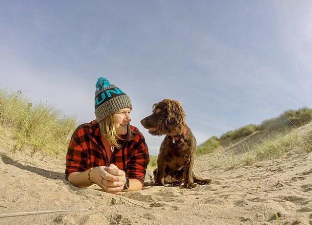 Девушка лежит на песке вместе с собакой
