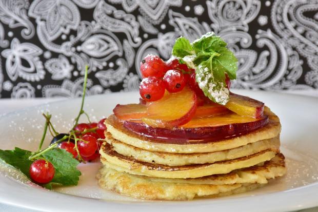 стопка блинчиков с медом и ягодами