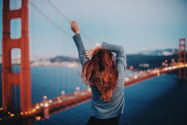 счастливая девушка любуется видом на город