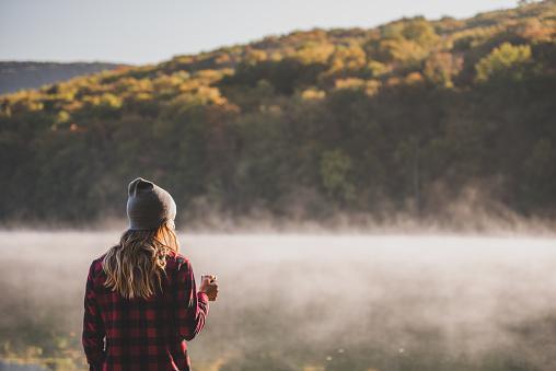 девушка в осенней одежде смотрит вдаль на природный пейзаж