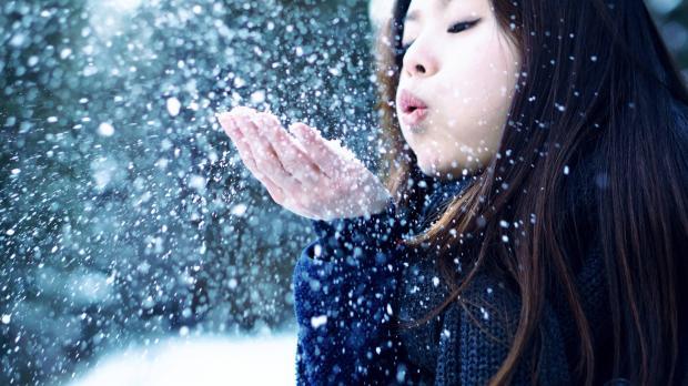 девушка сдувает снег с ладошек