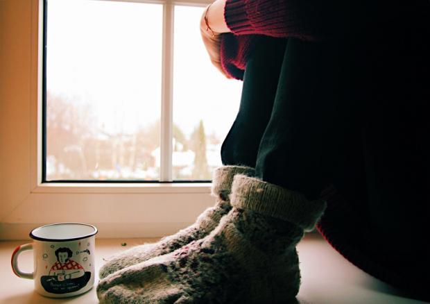 девушка сидит на подоконнике с чашкой чая