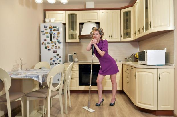 девушка стоит со шваброй в кухне