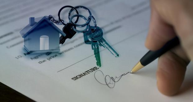 мужчина подписывает договор, ключи от дома