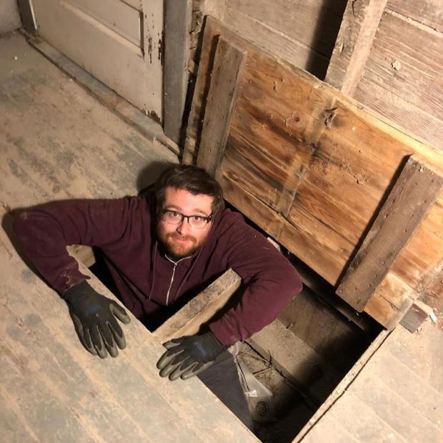 мужчина выглядывает из подвала дома