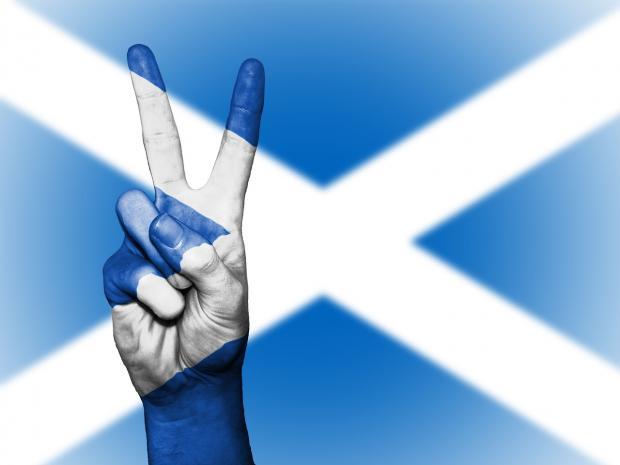 флаг Шотландии и рука человека