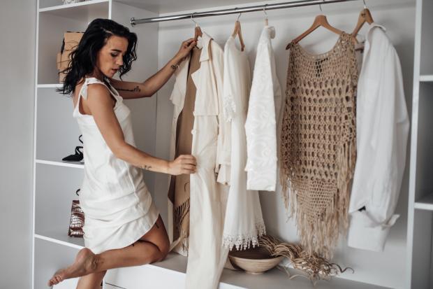 девушка рассматривает белые наряды в шкафу