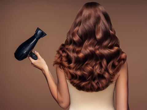 шикарные волнистые волосы у девушки с феном в руках