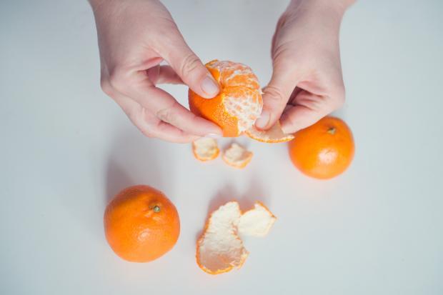 девушка чистит мандарин