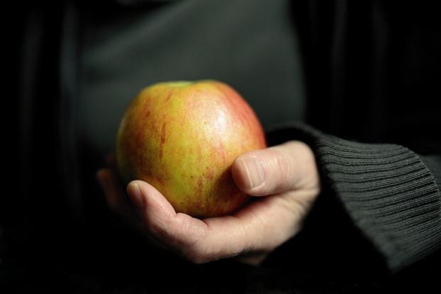 яблоко в ладони человека в черном свитере