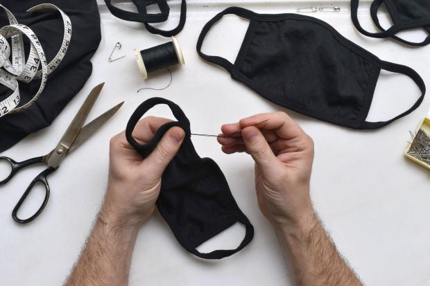 мужчина шьет маску для лица черного цвета