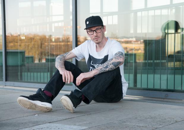 мужчина в кепке и очках сидит на тротуаре