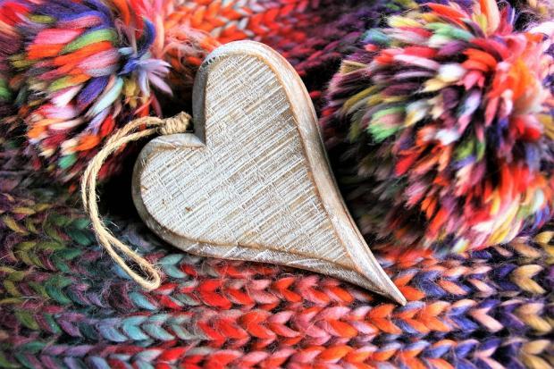 деревянная фигурка в виде сердца лежит на ярком шарфе