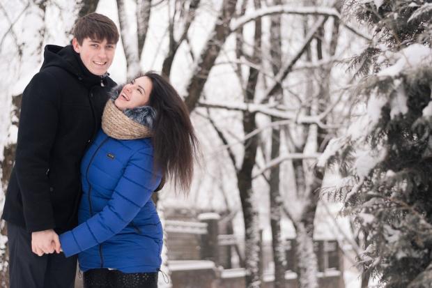 влюбленная пара стоит обнявшись на заснеженной аллее