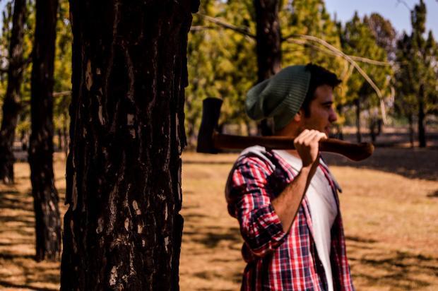 молодой человек в лесу с топором на плече