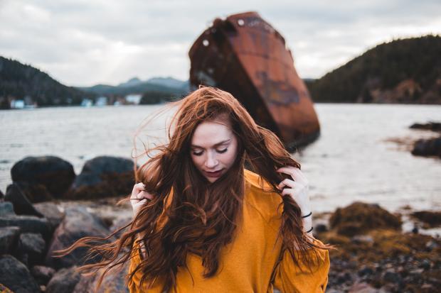 Длинноволосая девушка в желтом свитшоте стоит на берегу моря