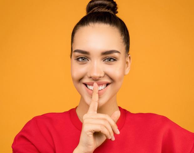 Темноволосая девушка в красном свитшоте держит указательный палец возле лица