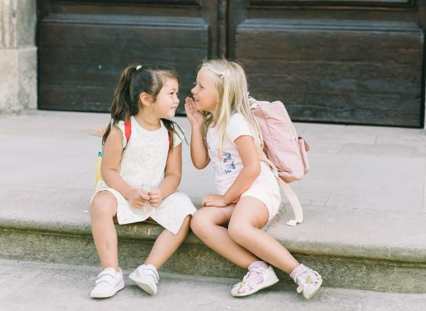 две маленькие девочки разговаривают сидя на ступеньках