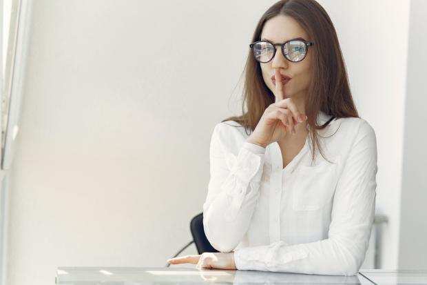 девушка в белой блузе и очках сидит за столом и держит указательный палец у лица