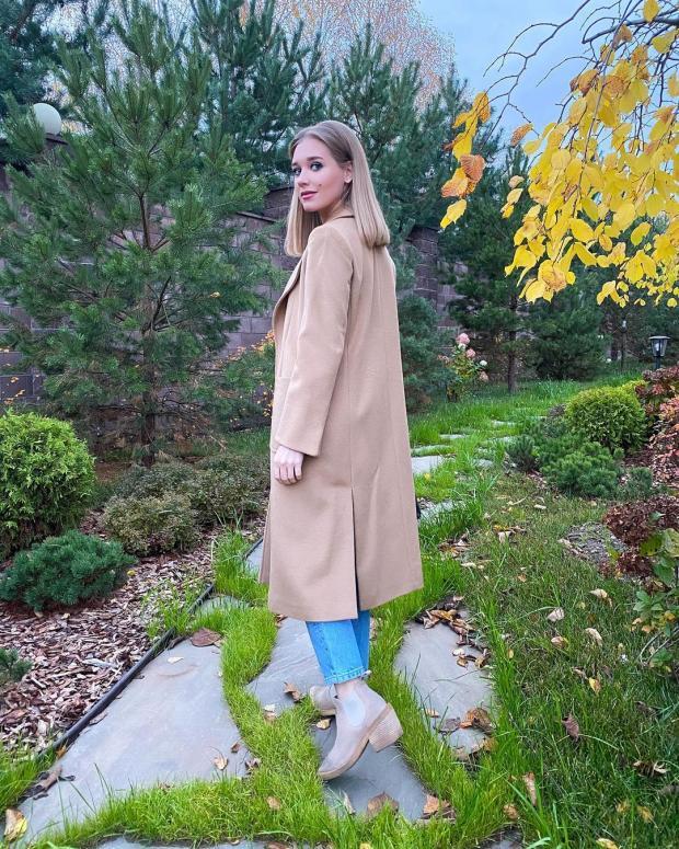 Кристина Асмус в коричневом пальто и синих джинсах