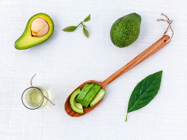 Авокадо и масло авокадо на белом столе и деревянной ложке