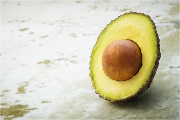 разрезанный авокадо на мраморной поверхности